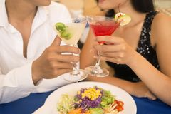 Romantic dinner. Couple clinking cocktails while having a romantic dinner Royalty Free Stock Photos