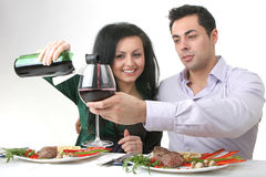 Romantic dinner. Couple having a romantic dinner with a grilled steak and a bottle of red wine stock image