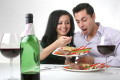 Romantic dinner. Couple having a romantic dinner with a grilled steak and a bottle of red wine Royalty Free Stock Photography
