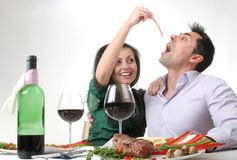 Romantic dinner. Couple having a romantic dinner with a grilled steak and a bottle of red wine. Female holding a piece of red pepper royalty free stock photos