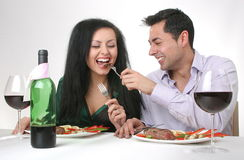 Romantic dinner. Couple having a romantic dinner with a grilled steak and a bottle of red wine. Male is feeding the woman Royalty Free Stock Photography