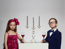 Romantic dinner with candles at the beautiful couple.kids. Romantic dinner with candles at the beautiful couple.beauty little girl in dress and boy in suit and Stock Photos