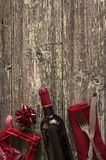 Romantic dinner concept. Bottle of red wine, vintage cutlery on red napkin,red wicker heart on old paint wooden background with copy space and sepia effect Royalty Free Stock Photos