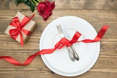 Romantic dinner concept. Festive table setting for Valentines Day on wooden background. Red rose and romantic gift. Top view. Romantic dinner concept. Festive Stock Photo