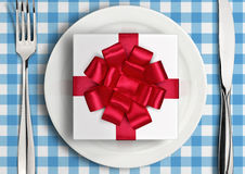 Romantic dinner concept, gift with ribbon on plate. Top view Stock Photos