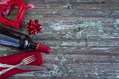 Romantic dinner concept. Red wicker heart,bottle of red wine,red napkin and cutlery on old paint wooden background with copy space Stock Photos