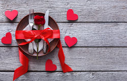 Romantic dinner concept. Valentine day or proposal background. Top view of restaurant wooden table with heart and rose with cutlery on plate. Copy space on Stock Photo