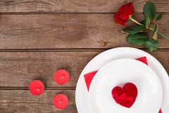 Romantic dinner concept. Valentine day or proposal background. Top view of restaurant wooden table with heart and rose with cutlery on plate. Copy space on Royalty Free Stock Photo