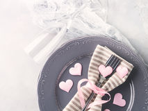Romantic dinner date plates hearts champagne glasses on gray Stock Photo