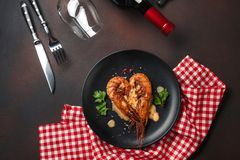 Romantic dinner with heart-shaped shrimps and wine on a brown background. Top view. With copy space royalty free stock images