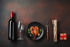 Romantic dinner with heart-shaped shrimps and wine on a brown background stock photo
