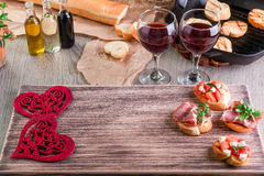 Romantic dinner. Love. Bruschetta set for wine with tomatoes, prosciutto, herbs and oil on wooden board. Valentine day. Royalty Free Stock Photo