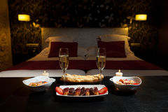 Romantic dinner in a luxurious hotel. Romantic dinner with champagne and candlelight in the bedroom stock photography