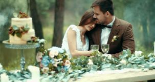 Romantic dinner in misty forest. Attractive sensitive loving couple in vintage cloth is tenderly hugging at table. Decorated with candles, leaves and flowers stock footage