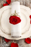 Romantic dinner: napkin ring made with red rose. Petals around the plate Royalty Free Stock Image