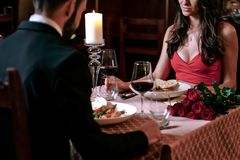 Romantic dinner in the restaurant. Attractive couple in love is dating and drinking wine during romantic dinner in the restaurant stock photo