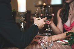 Romantic dinner in the restaurant. Couple in love holding hands and drinking wine during a romantic dinner in a restaurant reduced tone royalty free stock photography
