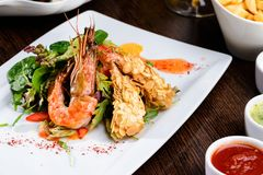 Romantic dinner at a restaurant. Delicious prepared shrimp with. Tomatoes, sauce and basil leaves stock photography