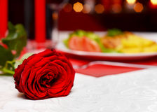 Romantic dinner. Rose on a table in front of delicious dishes at a romantic dinner Stock Photo