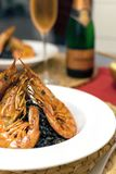 Romantic dinner, seafood risotto, rose champange. Valentines women day, romantic dinner - selective focus seafood risotto, black rice, king size shrimps, rose stock images