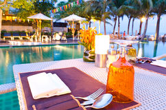 Romantic dinner set up table near pool Stock Photo