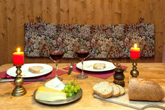 Romantic Dinner Setting. Intimate dinner table setting with candles and wine served in a romantic mountain chalet in the Alps Stock Photos