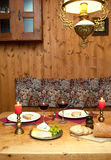 Romantic Dinner Setting. Intimate dinner table setting with candles and wine served in a romantic mountain chalet in the Alps Stock Images