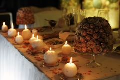 Romantic dinner setting. Some relaxing candles burning near bouquet on intimate dinner setting Royalty Free Stock Images