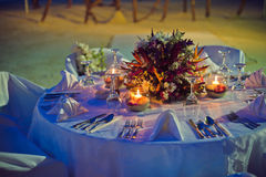 Romantic dinner setting on the beach at sunset Stock Photo