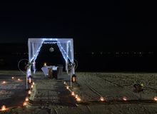 Romantic dinner setup on beach at night Royalty Free Stock Images