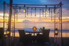 Romantic dinner setup on the beach. Sunset stock image