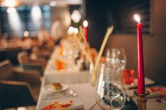 Romantic dinner setup, red decoration with candle light in a luxury gastro pub restaurant. Selective focus.  For celebrations and stock image