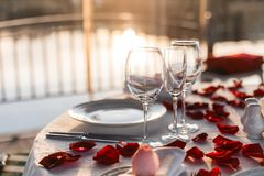 Romantic dinner setup, red decoration with rose petals in a restaurant royalty free stock photography