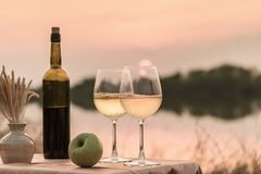 A romantic dinner in summer on a beach at sunset with two glasses of white wine. Alcohol alcoholism anniversary background beautiful beverage celebration royalty free stock photo