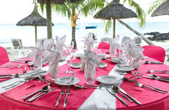 Romantic dinner on sunset beach. Pink table place setting Stock Photos