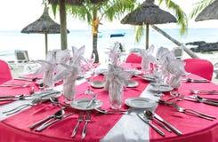 Romantic dinner on sunset beach. Pink table place setting. Romantic dinner on sunset beach. Festive pink table place setting. Selective focus Stock Photos