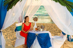 Romantic dinner at sunset on the beach . Young beautiful girl in Stock Photography