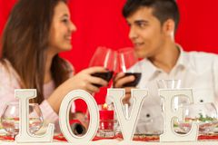 Romantic dinner table with couple in background. Royalty Free Stock Photo