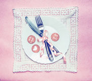 Romantic dinner table place setting with ribbon decoration and message cards on lace doily and pink background, top view. Stock Photography