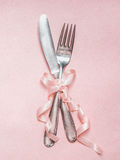 Romantic dinner table place setting with ribbon decoration on pink pale background, top view Royalty Free Stock Images