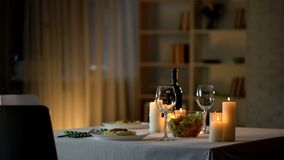 Romantic dinner table setting, wine glasses and fresh salad in bowl, home date. Stock photo royalty free stock images