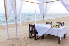 Romantic dinner table for three at a sandy beach in Thailand. Table with white tablecloths and veils on the Silver beach Koh Samui, Thailand Stock Image
