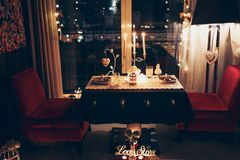 Romantic dinner for two. A romantic dinner for two in a restaurant with a view of the night city. Candle and heart decoration stock image