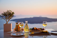 Romantic dinner for two at sunset.Greece, Santorin. I, restaurant on the beach, above the volcano Stock Photos