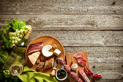 Romantic dinner with wine, cheese and traditional sausages Stock Photos