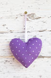 Romantic dotted heart shape hanging above white wooden surface o royalty free stock image