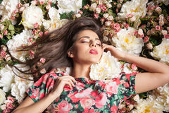 Romantic and dreammy woman lying down on flowers Stock Image