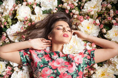 Romantic and dreammy woman lying down on flowers Stock Photos