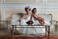 Romantic Duet. Lovely brides in a reception hotel having a large flowers bun hair Royalty Free Stock Image