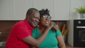 Romantic elderly black couple embracing indoors